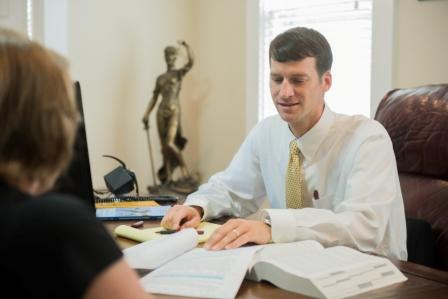 Travis Studdard meets with a client about her workers compensation case
