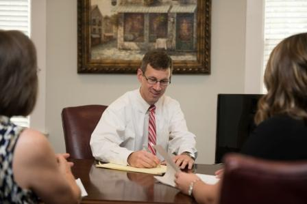 Jason Perkins discusses a workers' compensation case with a client and the client's family member