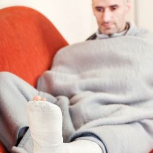 Many with leg injury rests leg on sofa arm